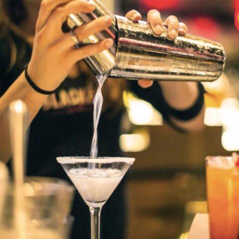 Image shows a bartender preparing drinks